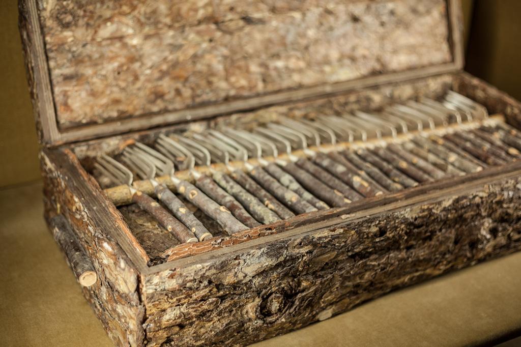 Scatola in corteccia d'albero che ospita al suo interno un servizio di posate con manico in legno di melo selvatico e argento.