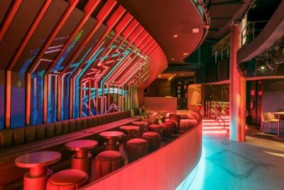Luci soffuse, pavimenti di marmo e tavolini con lampade dedicate. L'atmosfera è quella di un night club d'altri tempi, ma questo fascino sixties ben si armonizza con il modernissimo ledwall sullo sfondo.