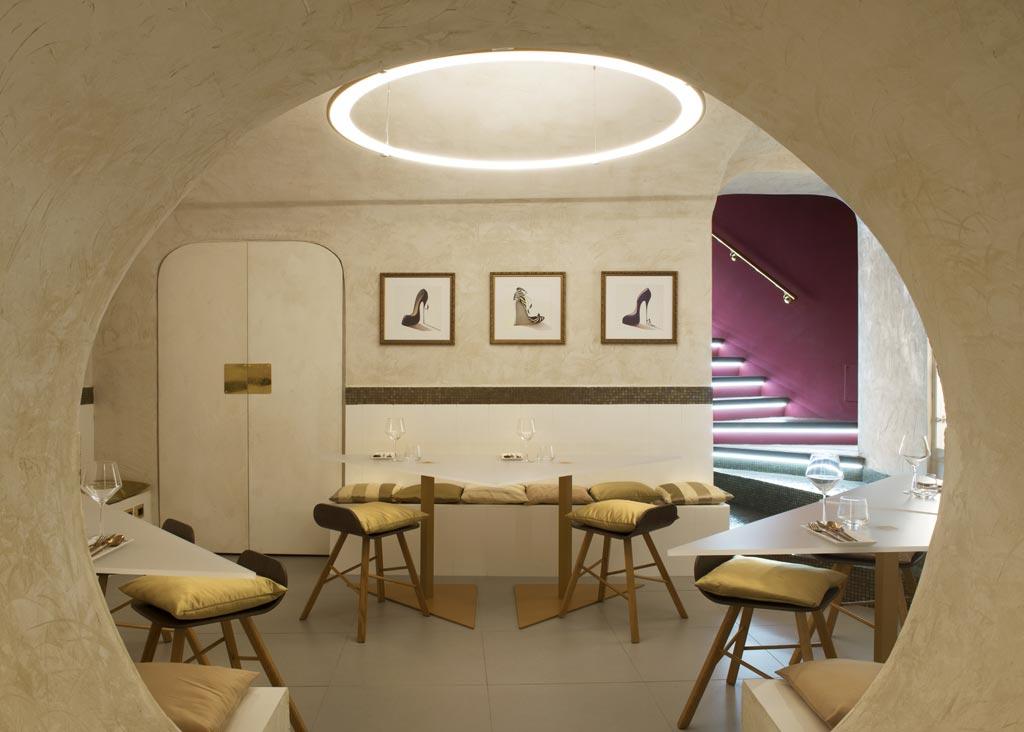 """Nel seminterrato, la saletta dorata con tavolini triangolari permette di """"spiare"""" gli chef al lavoro."""