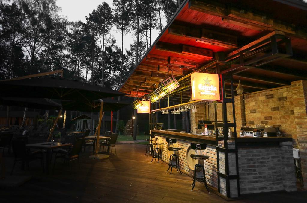 Il bar esterno si apre su un patio ed è circondato da una grande foresta di pini.