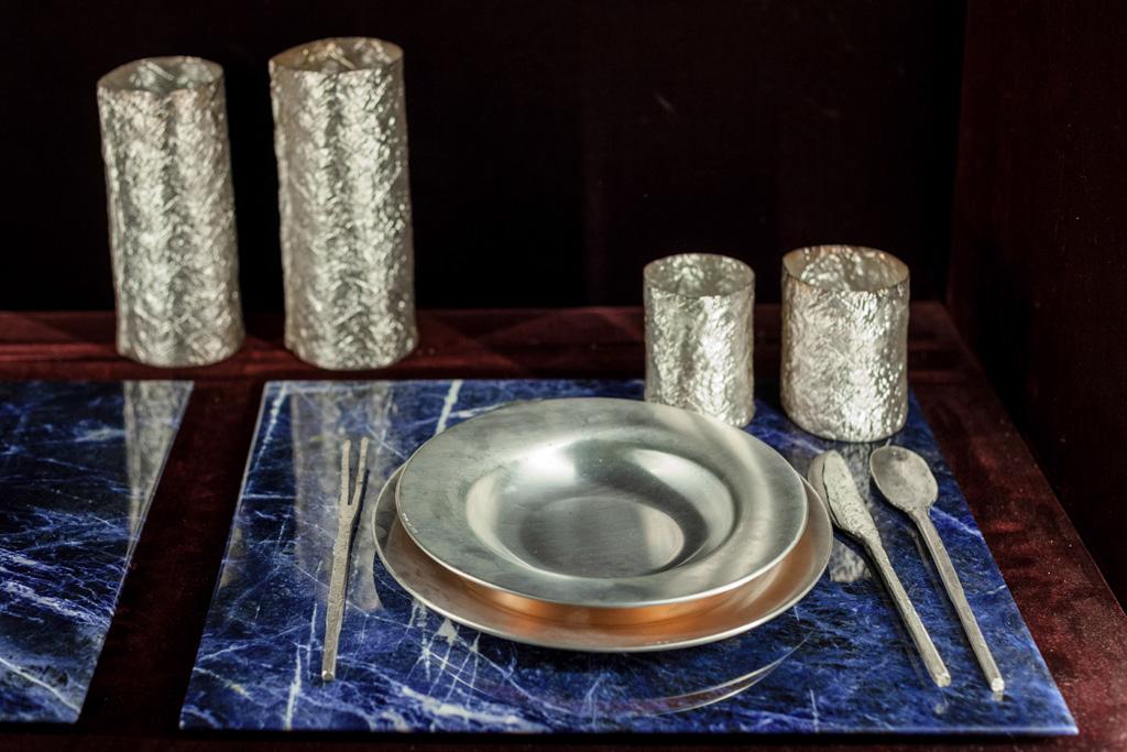 Un set di piatti fondi e piani realizzati in argento e rame e posate in argento massiccio martellate a mano posano su preziose tovagliette in marmo di una particolare colorazione blu sodalite.